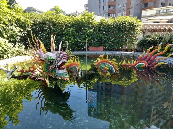 A very colorful Chinese dragon sculpture in an artificial pond. The dragon is made out of some very bright material that might be tile or colored plastic.