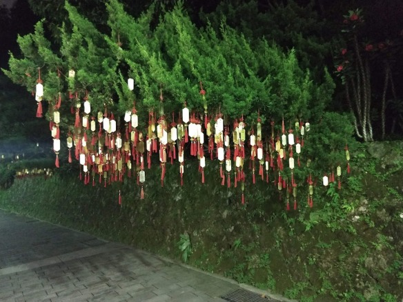 Many shiny gold tags with red tassles hanging from a bush.