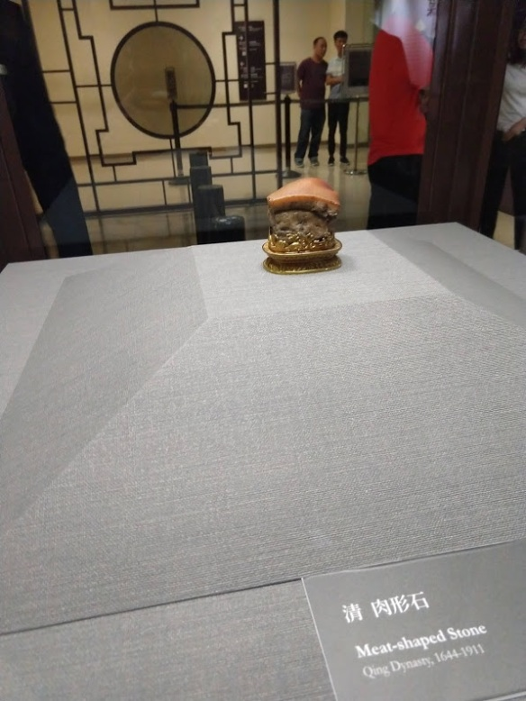 A picture of a carving in a display case that looks like a piece of pork belly.