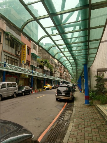 A Taipei street, with a narrow sidewalk sheltered by a greenish awning.