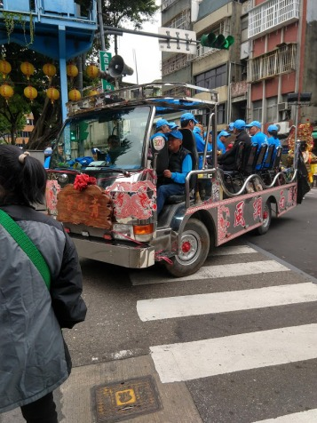 A truck with an open bed and a bunch of old people in chairs. They're all wearing matching blue jackets and baseball caps.