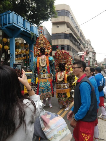 Two people in elaborate costumes with masks and fancy headdresses. One is tall and thin, one is short and squat.