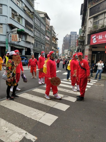 People dressed in red (long-sleeved t-shirts, sweat pants, and caps or scarves) with painted faces. Some are holding large fans.