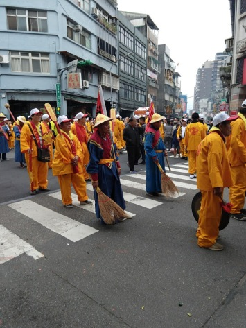 People dressed in yellow (loose jacket-like tops, yellow pants) and carrying paddle-like things over their shoulders, plus two people who are wearing blue with brooms and conical straw hats.