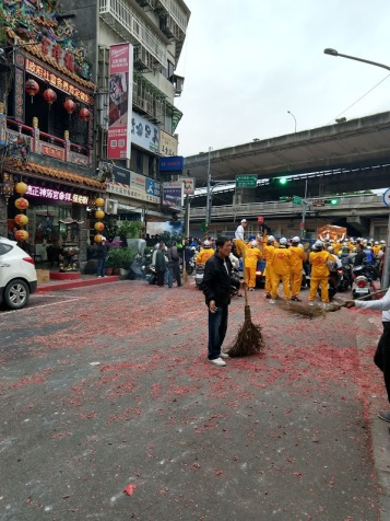 A man with a broom sweeping up a huge quantity of tiny red balls (which are spent fireworks lying in the street). You can see the people in yellow from the parade beyond him, moving on.