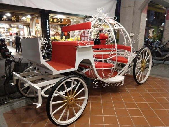 A Cinderella-esque carriage, sitting empty and unattended.