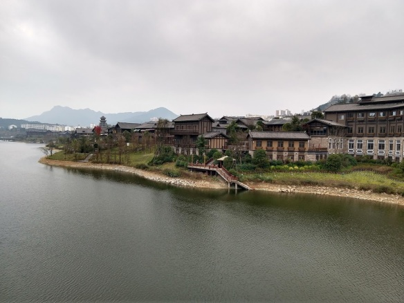 Buildings along a river. They're wood and stone, and fairly traditional in style. In the far distance, you can see mountains, and also modern-style tall buildings.