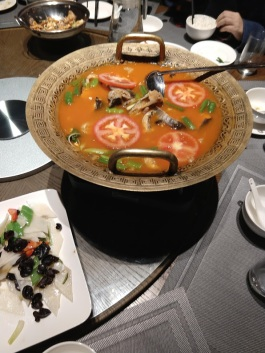 A decorative basin filled with a red soup; you can see slices of tomatoes and chunks of fish in it.