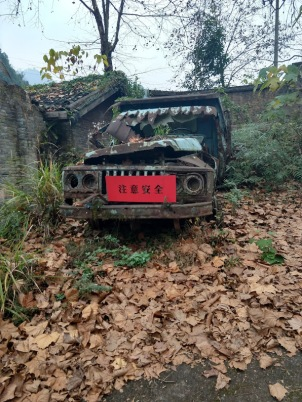 A very rusted-out truck with a red placard on the front that says something in Chinese.
