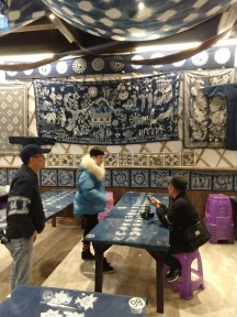 An art classroom with the walls and ceiling hung with batiks, all using a blue dye about the color of denim.