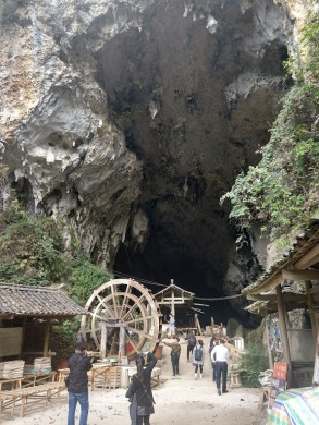 A natural cave rising up over a water wheel.