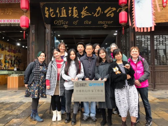 "A group of writers (some Chinese, some white) holding a sign and standing in front of a building with an ""Office of the Mayor"" sign on it."