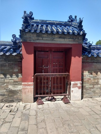 A fancy door, topped with fancy blue tiles on the roof, with a barricade in front of it.