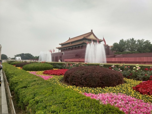Foreground: flowers and fountains. Background: wall and one of the palaces of the Forbidden City.