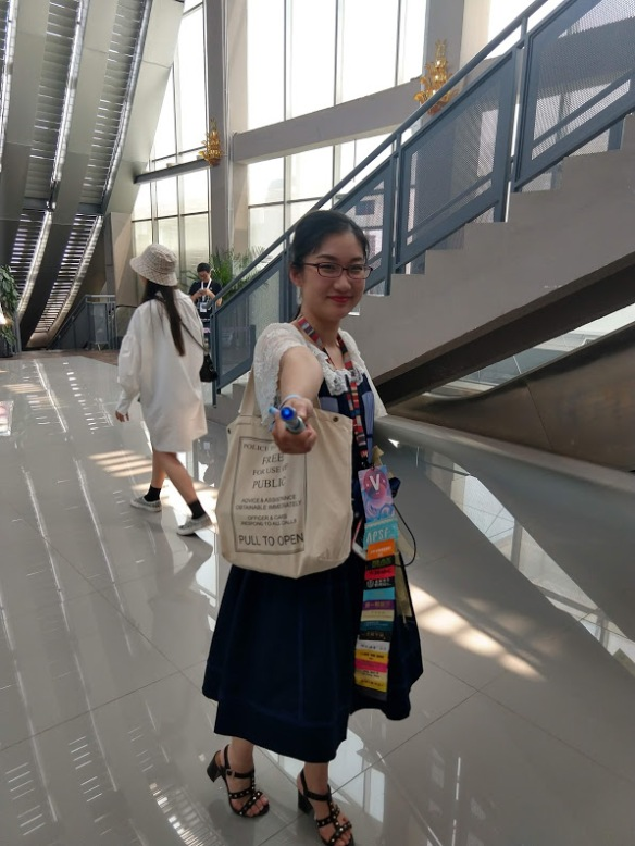 A young, smiling Chinese woman, carrying a Dr. Who themed tote bag, wearing a bunch of badge ribbons, and pointing a sonic screwdriver at the camera.