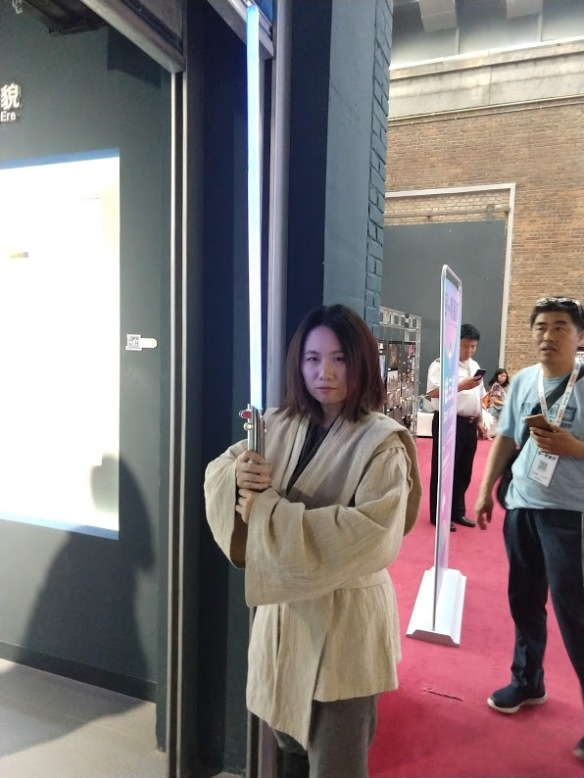 A Chinese woman in Jedi robes, holding a lightsaber upright.