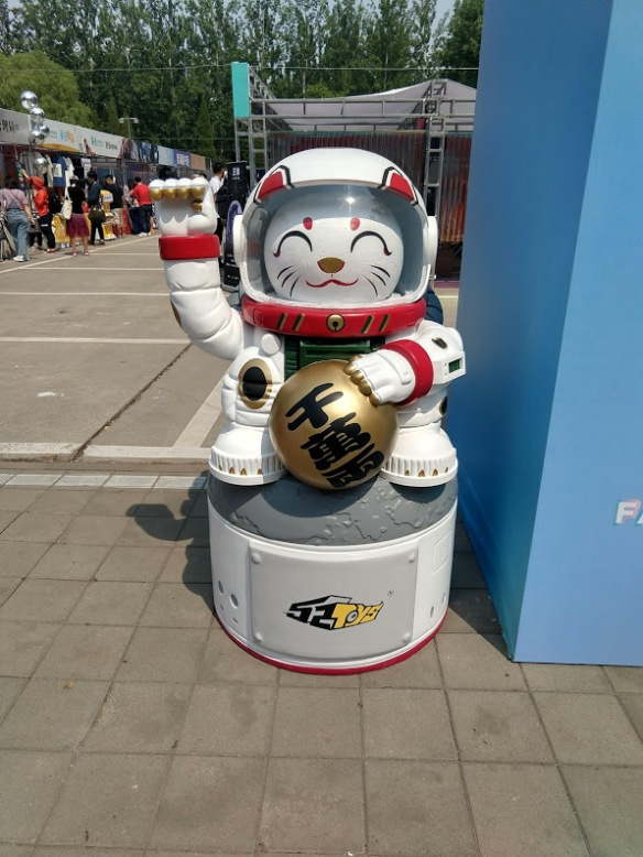 A lucky cat in an astronaut suit, arm raised, holding a ball. It's quite large.