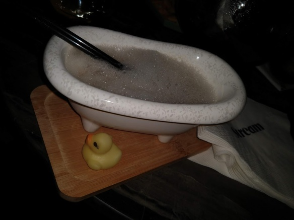 A miniature bathtub filled with foam. Two straws are sticking out. The bathtub rests on a wooden cutting board, which also holds a rubber duckie.