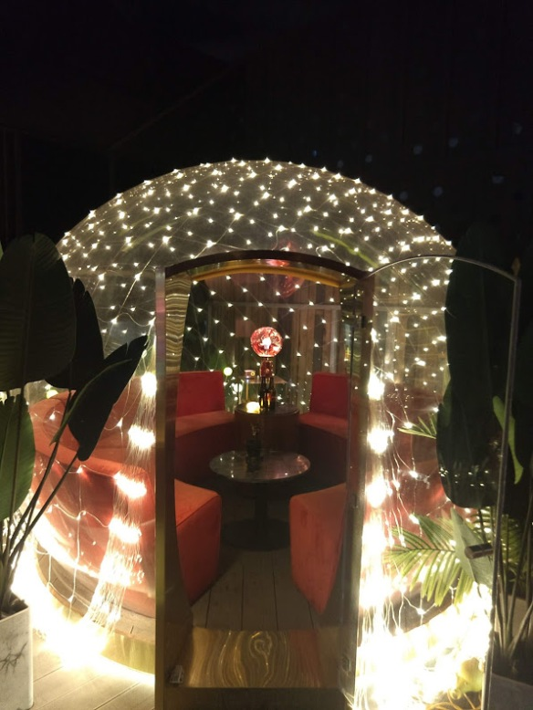 A plastic igloo thing lit up with white mini lights. Inside, you can see round bench seats around a low table.