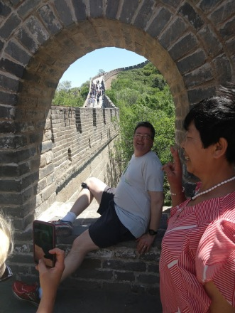 Ed, posing in a brick window overlooking the Great Wall; next to him is a Chinese lady, posing with Ed but smiling for a camera off to the side.