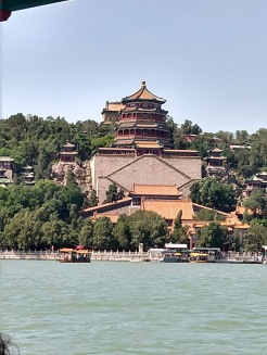 The Tower of Buddhist Incense, which is set into a big hill, seen from out on a lake.