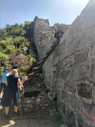 Crystal and the guide, Linda, are standing at the base of a homemade ladder leaning up against a section of the Great Wall.