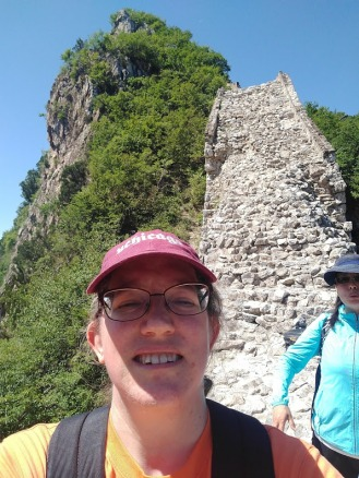 A selfie of me, with Linda in the background and a section of wall that looks like a vertical rockfall, basically.