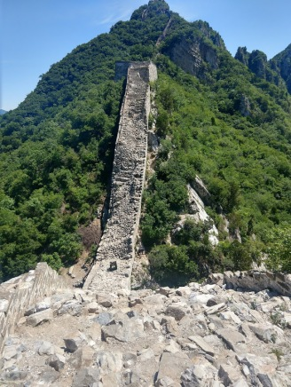 The Great Wall of China, looking a lot more ruined and wild than at Badaling, surrounded by green forests.