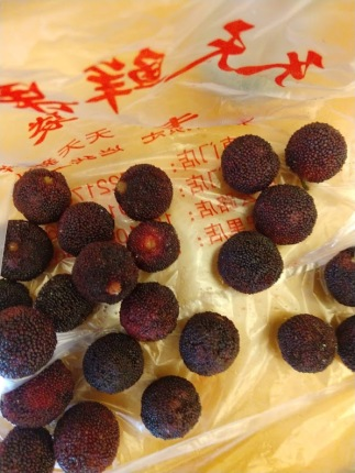 Round, dark-red fruits with what looks like a bumpy skin.