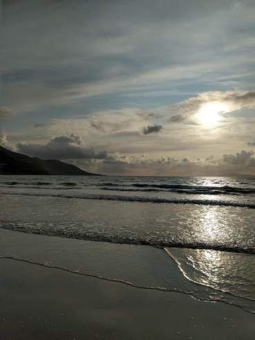 The sun low in the sky, partially obscured by clouds, over a beach.