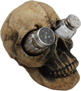 A fairly realistic fake human skull, with a salt and pepper shaker in the eye sockets.